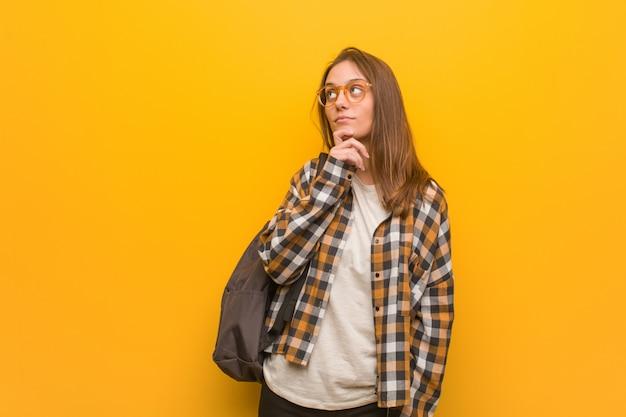 Młoda studencka kobieta wątpi i wprawiać w zakłopotanie