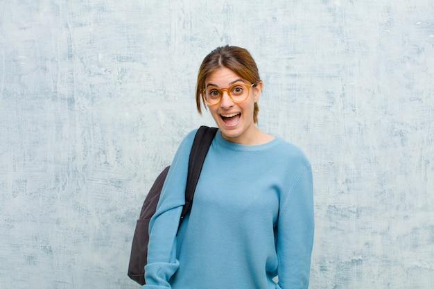 Młoda studencka kobieta wyglądająca na szczęśliwą i mile zaskoczoną, podekscytowaną zafascynowanym i zszokowanym wyrazem twarzy na tle ściany grunge