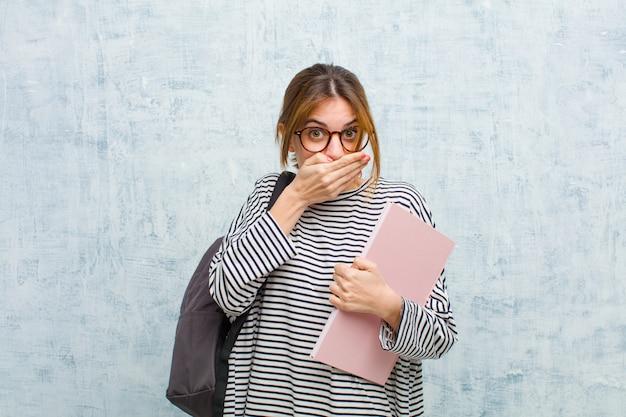 Młoda studencka kobieta zakrywa usta rękami z zszokowanym, zdziwionym wyrazem, utrzymuje w tajemnicy lub mówi ups