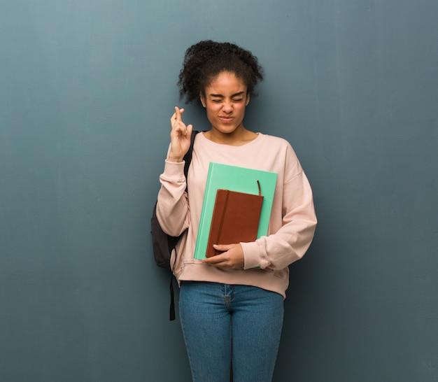 Młoda studencka murzynka krzyżuje palce dla mieć szczęście. ona trzyma książki.