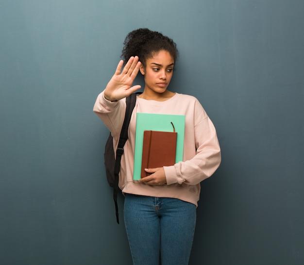 Młoda studencka murzynka stawia rękę w przodzie. ona trzyma książki.