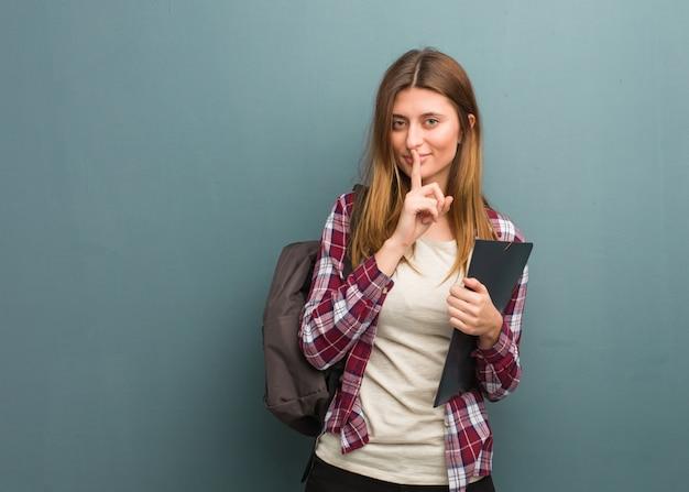 Młoda studencka rosyjska kobieta utrzymuje sekret lub pyta dla ciszy