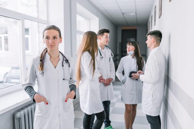 Młoda student medycyny pozycja w korytarzu z kolegami