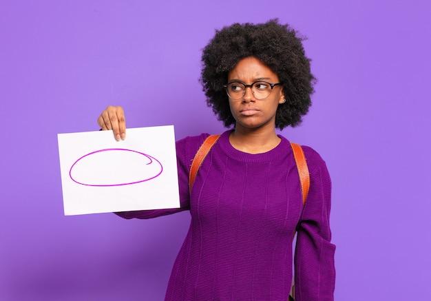 Młoda studentka afro czuje się smutna, zdenerwowana lub zła i patrzy w bok z negatywnym nastawieniem, marszcząc brwi w niezgodzie