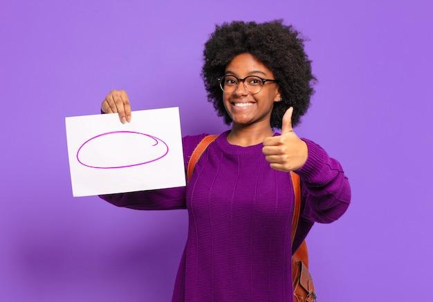 Młoda studentka afro kobieta czuje się dumna, beztroska, pewna siebie i szczęśliwa, uśmiechając się pozytywnie z kciukami w górę
