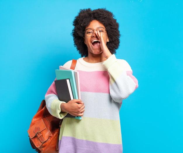 Młoda studentka afro kobieta czuje się szczęśliwa, podekscytowana i pozytywna, wydając głośny okrzyk z rękami przy ustach