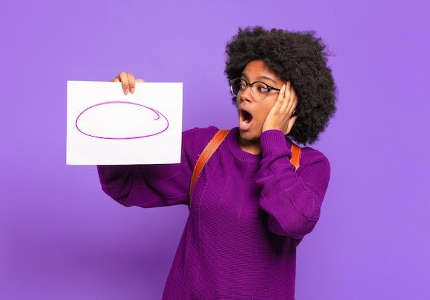 Młoda studentka afro kobieta czuje się szczęśliwa, podekscytowana i zaskoczona, patrząc w bok z obiema rękami na twarzy