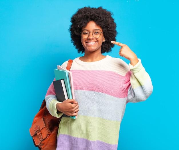 Młoda studentka afro kobieta uśmiecha się pewnie, wskazując na swój szeroki uśmiech, pozytywne, zrelaksowane, zadowolone nastawienie