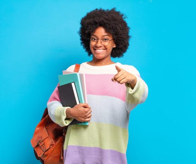 Młoda studentka afro kobieta wskazując na aparat z zadowolonym, pewnym siebie, przyjaznym uśmiechem, wybierając ciebie