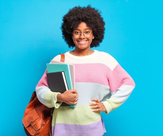 Młoda studentka afro uśmiechnięta radośnie z ręką na biodrze i pewną siebie, pozytywną, dumną i przyjazną postawą