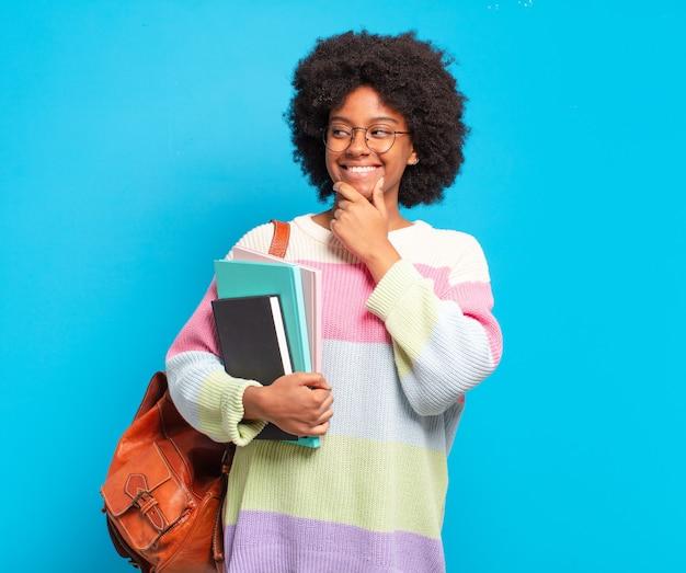 Młoda studentka afro uśmiechnięta ze szczęśliwym, pewnym siebie wyrazem twarzy z ręką na brodzie, zastanawiająca się i patrząca w bok