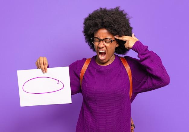 Młoda studentka afro wygląda na niezadowoloną i zestresowaną, samobójczy gest wykonujący znak pistoletu ręką, wskazujący na głowę