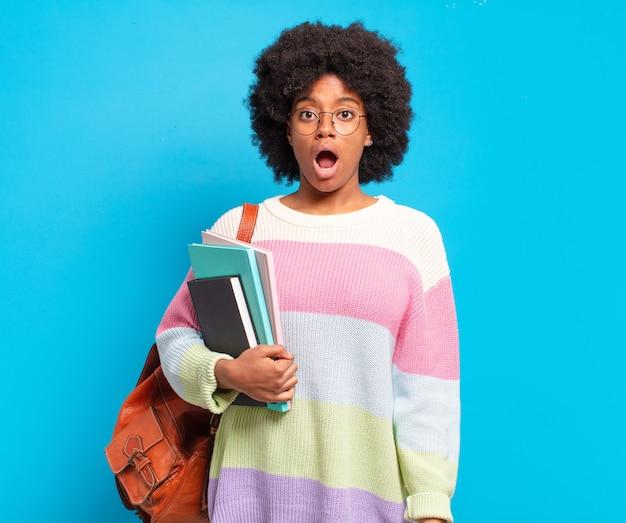 """Młoda studentka afro wyglądająca na bardzo zszokowaną lub zaskoczoną, patrząca z otwartymi ustami i mówiąca """"wow"""