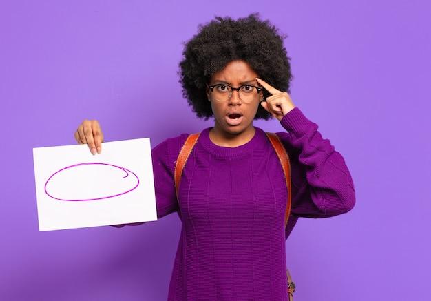 Młoda studentka afro wyglądająca na zaskoczoną, z otwartymi ustami, zszokowaną, realizującą nową myśl, pomysł lub koncepcję