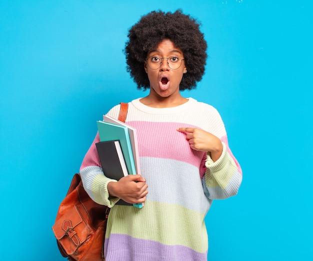 Młoda studentka afro wyglądająca na zszokowaną i zaskoczoną z szeroko otwartymi ustami, wskazująca na siebie