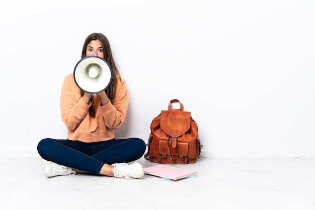 Młoda studentka brazylijska kobieta siedzi na podłodze krzycząc przez megafon