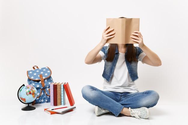 Młoda studentka brunetka w dżinsowych ubraniach zakrywających twarz z książką czytającą siedzącą w pobliżu kuli ziemskiej, plecaka, podręczników szkolnych na białym tle