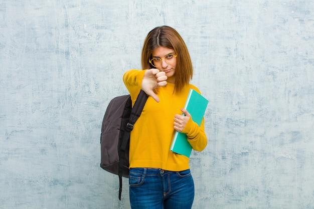 Młoda studentka czuje się krzyża, zła, zirytowana, rozczarowana lub niezadowolona, pokazując kciuk w dół z poważnym spojrzeniem na ścianę grunge
