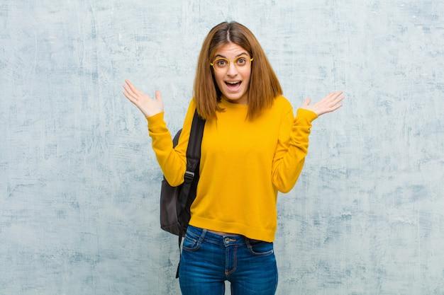 Młoda studentka czuje się szczęśliwa, podekscytowana, zaskoczona lub zszokowana, uśmiechnięta i zdziwiona czymś niewiarygodnym