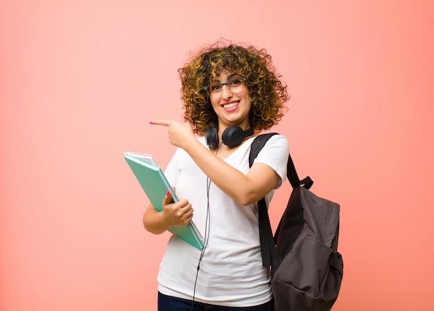 Młoda studentka czuje się szczęśliwa, zszokowana i zaskoczona, zakrywając usta ręką i wskazując na boczną przestrzeń kopii na różowej ścianie