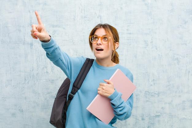 Młoda studentka czuje się zszokowana i zaskoczona, wskazując i patrząc z podziwem na zdumiony, otwarty wyraz twarzy