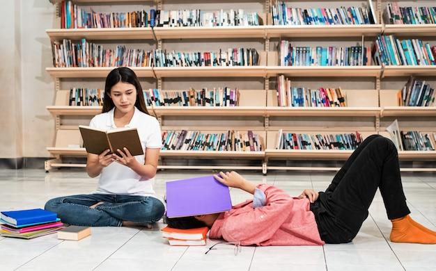 Młoda studentka czytająca książkę, jej przyjaciółka kładąca się i śpiąca, wykonująca wspólnie czynności, w bibliotece, wokół rozmazane światło