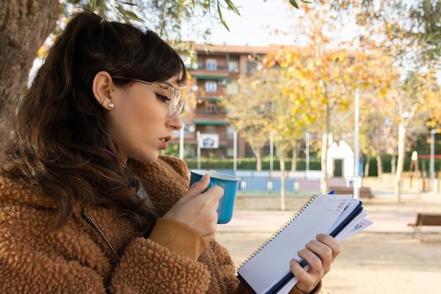 Młoda studentka dziewczyna w okularach konsultując jej program w parku.