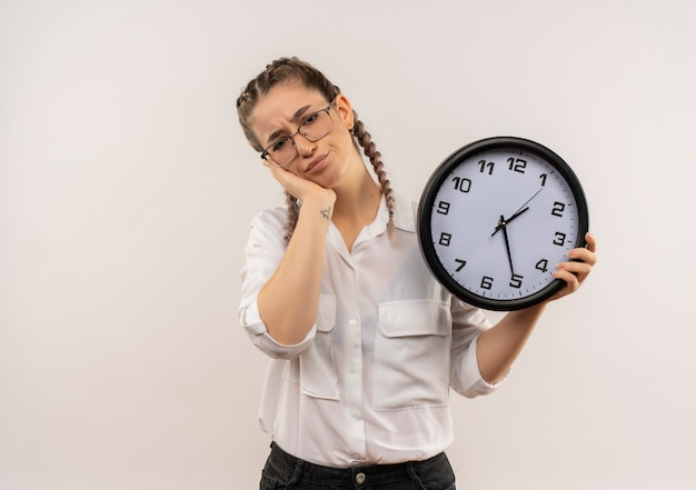 Młoda studentka dziewczyna w okularach z warkoczykami w białej koszuli trzyma zegar ścienny patrząc do przodu zmęczony i znudzony stojąc nad białą ścianą