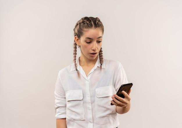 Młoda studentka dziewczyna z warkoczykami w białej koszuli, patrząc na ekran swojego telefonu komórkowego z niejasnym wyrazem stojącym na białej ścianie