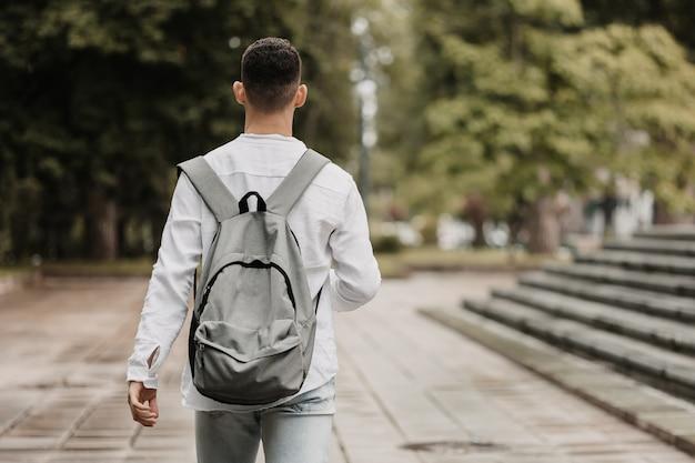Młoda studentka idzie na uniwersytet strzał od tyłu