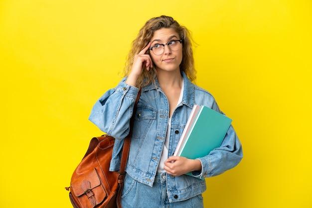 Młoda studentka kaukaska kobieta na białym tle na żółtym tle, mająca wątpliwości i myśląca