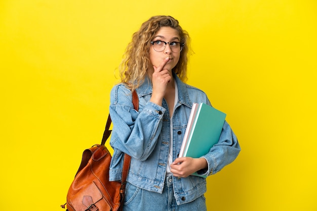 Młoda studentka kaukaska kobieta na białym tle na żółtym tle, mająca wątpliwości podczas patrzenia w górę