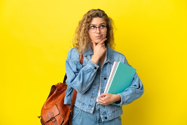 Młoda studentka kaukaska kobieta na białym tle na żółtym tle mająca wątpliwości