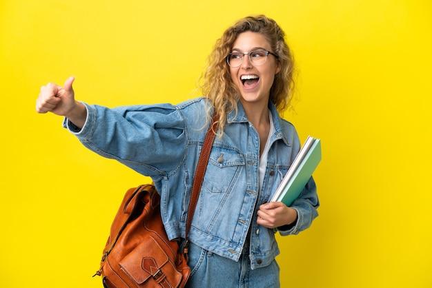 Młoda studentka kaukaska kobieta odizolowana na żółtym tle dająca gest kciuka w górę
