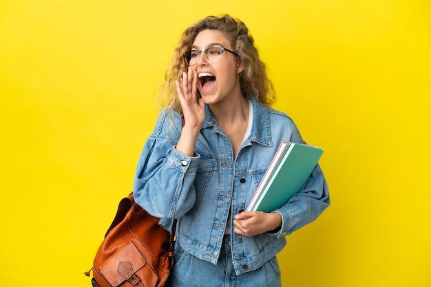 Młoda studentka kaukaska kobieta odizolowana na żółtym tle krzycząca z szeroko otwartymi ustami