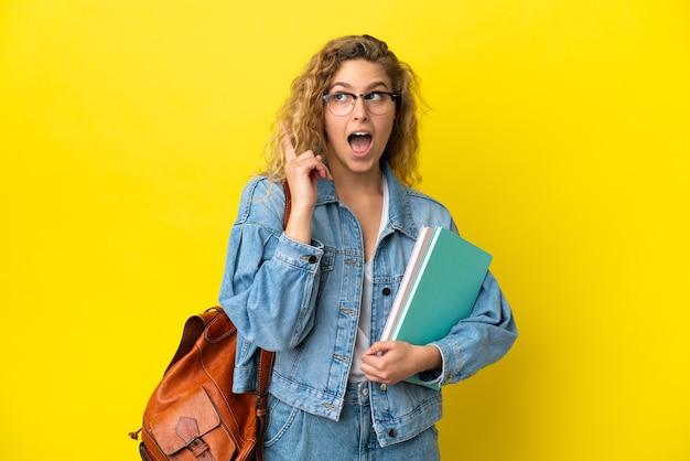 Młoda studentka kaukaska kobieta odizolowana na żółtym tle myśląca o pomyśle wskazującym palec w górę