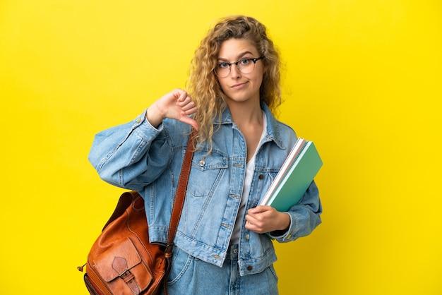 Młoda studentka kaukaska kobieta odizolowana na żółtym tle pokazując kciuk w dół z negatywnym wyrażeniem