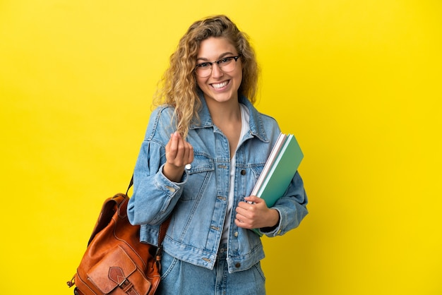 Młoda studentka kaukaska kobieta odizolowana na żółtym tle robi pieniądze gest