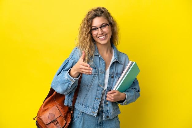 Młoda studentka kaukaska kobieta odizolowana na żółtym tle, ściskając ręce, aby zamknąć dobrą ofertę