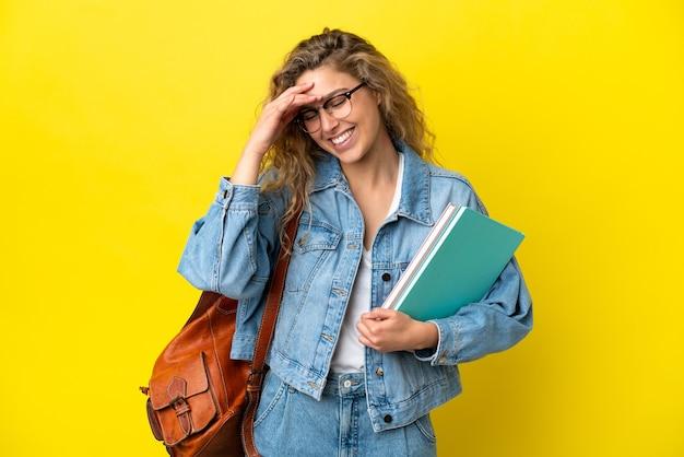 Młoda studentka kaukaska kobieta odizolowana na żółtym tle śmiejąc się