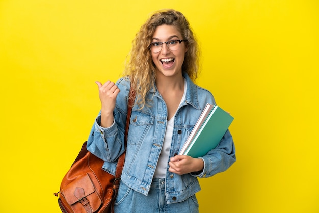 Młoda studentka kaukaska kobieta odizolowana na żółtym tle wskazująca na bok, aby zaprezentować produkt