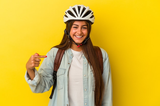 Młoda studentka kaukaska kobieta w kasku rowerowym na żółtym tle osoba wskazująca ręcznie na miejsce na koszulkę, dumna i pewna siebie