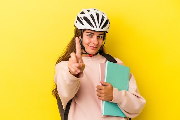 Młoda studentka kaukaski kobieta nosi kask rowerowy na białym tle na żółtym tle pokazując numer jeden palcem.