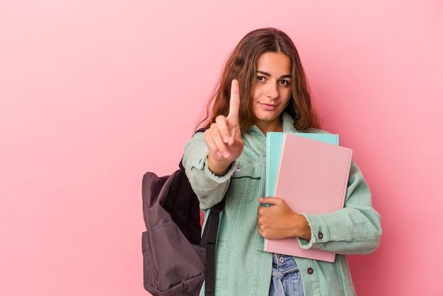 Młoda studentka kaukaski kobieta trzyma książki na białym tle na różowym tle pokazując numer jeden z palcem.