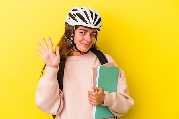 Młoda studentka kaukaski kobieta w kasku rowerowym na białym tle na żółtym tle uśmiechający się wesoły pokazując numer pięć palcami.