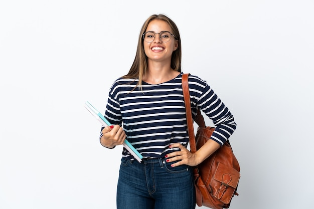 Młoda studentka kobieta na białym tle na białej ścianie pozowanie z rękami na biodrze i uśmiechnięty