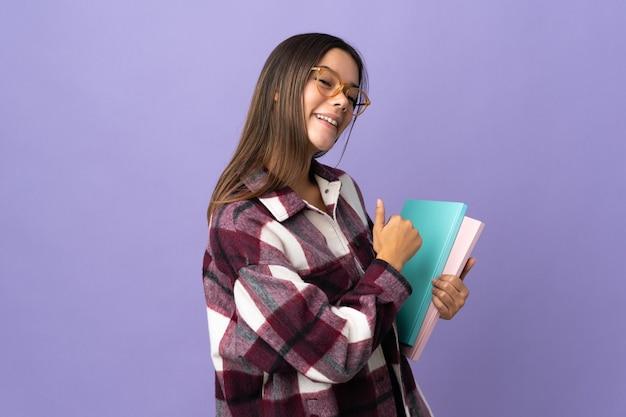 Młoda studentka kobieta na białym tle na fioletowy dumny i zadowolony z siebie