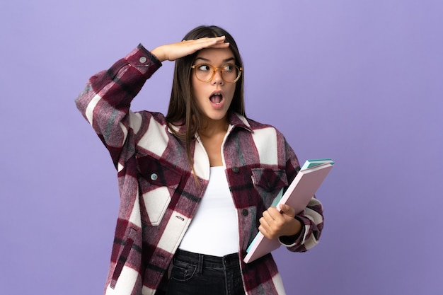 Młoda studentka kobieta na białym tle na fioletowy robi gest niespodzianki, patrząc w bok