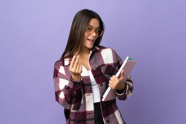 Młoda studentka kobieta na białym tle na fioletowy robi pieniądze gestowi