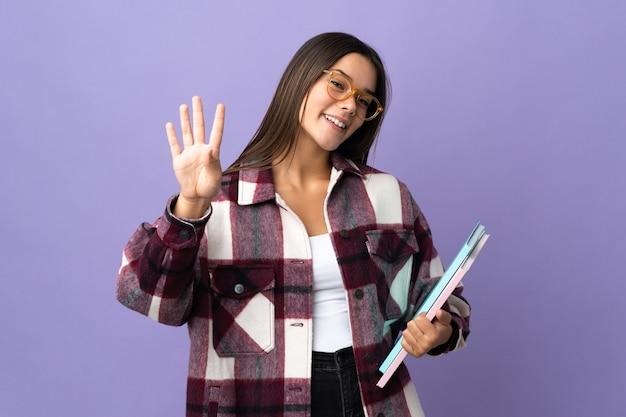 Młoda studentka kobieta na białym tle na fioletowy szczęśliwy i licząc cztery palcami